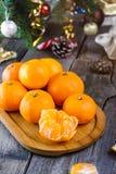 Le concept de Noël avec des mandarines, sapin s'embranche avec le décor, les cadeaux et les épices sur la vieille table en bois r Photo libre de droits