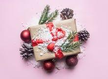 Le concept de nouvelle année, une boîte avec un cadeau, jouets de Noël-arbre sont présentés sur un fond rose avec la configuratio image libre de droits
