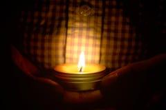 Le concept de prière et d'espoir de la bougie s'allument dans des mains Photo stock