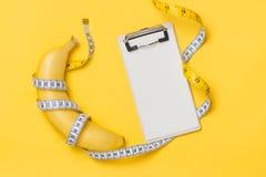 Le concept de régime, de forme physique et de santé a présenté par l'enveloppe jaune de banane Image libre de droits