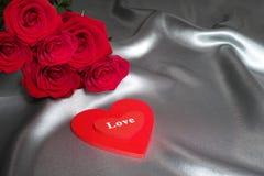 Le concept de Saint-Valentin, concept de fête des mères, les roses rouges sur le fond gris en soie avec les coeurs rouges aiment Image stock