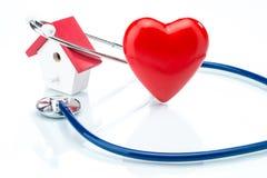Le concept de soin de famille, le modèle de maison et le coeur forment avec le stethoscop Image stock