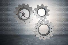Le concept de travail d'équipe avec des roues dentées et des gens d'affaires Images libres de droits