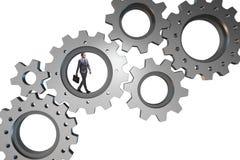 Le concept de travail d'équipe avec des roues dentées et des gens d'affaires Photo stock