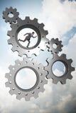Le concept de travail d'équipe avec des roues dentées et des gens d'affaires Photographie stock libre de droits