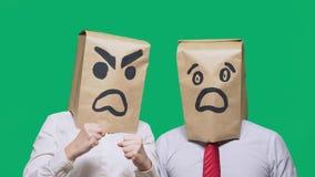 Le concept des émotions et des gestes Deux personnes dans des sacs en papier avec des sourires Le smiley agressif jure  photos stock
