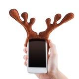 Le concept drôle de Noël de Smartphon, andouillers de renne jouent, d'isolement sur le blanc photo libre de droits
