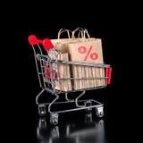 Le concept du chariot à achats avec des sacs en papier est isolé sur le noir Photo stock
