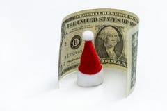 Le concept du coût de célébrer la nouvelle année et le Noël Un dollar autour des chapeaux rouges de Santa Claus sur un fond blanc images stock