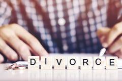 Le concept du divorce Le mot - divorcez les anneaux dans le premier plan, un jeune homme dans un règlement signé de divorce de ch Image libre de droits