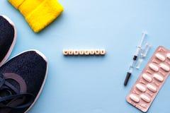 le concept du dopage dans le sport Médecine d'inscription sur un fond bleu Chaussures de sports, pilules, seringue avec la médeci image libre de droits
