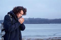Le concept du froid, givrent le jeune homme d'une chevelure bouclé chauffant le sien images stock