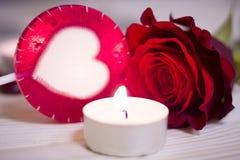 Le concept du jour de StValentine avec une rose et une bougie rouges Photographie stock