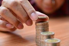 Le concept et la main d'argent d'économie mettant la pièce de monnaie d'argent empilent f croissant Photo libre de droits