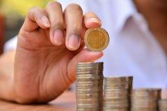 Le concept et la main d'argent d'économie mettant la pièce de monnaie d'argent empilent f croissant Images libres de droits