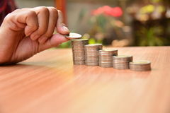 Le concept et la main d'argent d'économie mettant la pièce de monnaie d'argent empilent f croissant Image libre de droits