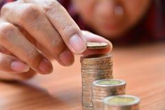 Le concept et la main d'argent d'économie mettant la pièce de monnaie d'argent empilent f croissant Image stock