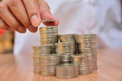 Le concept et la main d'argent d'économie mettant la pièce de monnaie d'argent empilent f croissant Photo stock