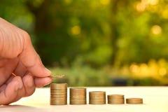 Le concept et la main d'argent d'économie mettant la pièce de monnaie d'argent empilent f croissant Photos libres de droits