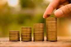 Le concept et la main d'argent d'économie mettant la pièce de monnaie d'argent empilent f croissant Images stock