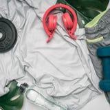 Le concept folâtre le mode de vie, vêtements de sport, écouteurs, haltères, rayées sur un fond blanc, avec la bouteille de l'eau  Images stock