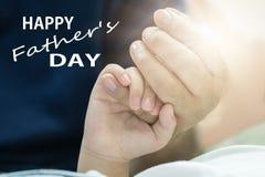 Le concept, le père et le fils de jour de pères tiennent des mains avec amour Image stock