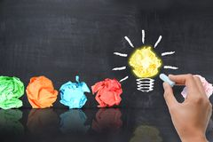 Le concept lumineux d'idée avec l'ampoule formée a chiffonné le papier sur le tableau noir photo libre de droits
