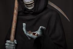 Le concept : mise à mort de drogues Faucheuse tenant la seringue avec des drogues Image stock