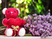 Le concept pour l'amour le jour de valentines, ours de nounours reposent la prise le coeur rouge par le côté avec le bouquet des  Photos libres de droits