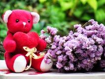 Le concept pour l'amour le jour de valentines, ours de nounours reposent la prise le coeur rouge par le côté avec le bouquet des  Photographie stock