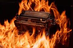 Le concept a tiré de la machine à écrire manuelle antique avec le papier brûlant sur le fond noir, foyer sélectif Photo stock