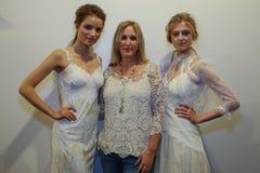 Le concepteur Claire Pettibone pose avec des modèles à l'exposition 2016 de piste de Claire Pettibone Bridal solides solubles Image libre de droits