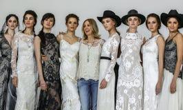 Le concepteur Claire Pettibone pose avec des modèles à l'exposition 2016 de piste de Claire Pettibone Bridal solides solubles Photographie stock