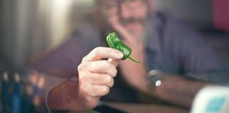 Le concepteur créatif regarde le poivron vert, poivre de piment fort Image libre de droits