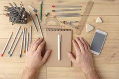 Le concepteur dessine un croquis dans un carnet sur une table en bois papeterie Vue de ci-avant photographie stock libre de droits