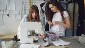 Le concepteur féminin de jeune femme travaille avec la machine à coudre tandis que son associé regarde des points et choisit des  banque de vidéos