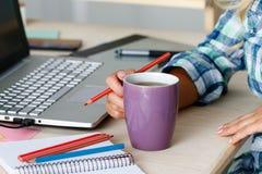 Le concepteur féminin remet tenir la tasse de la boisson chaude et dessiner des WI Image libre de droits