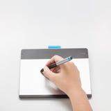 Le concepteur ou le retoucher remet l'écriture sur le comprimé numérique Photo stock