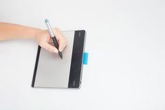 Le concepteur remet l'écriture sur le comprimé numérique Image stock