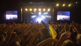 Le concert de musique en direct, beaucoup de fans ondulent des mains sur le festival de roche contre l'étape brillamment allumée  banque de vidéos