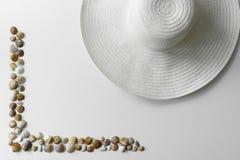 Le conchiglie incorniciano ed espongono al sole il cappello di paglia fotografia stock