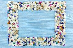 Le conchiglie incorniciano su fondo blu di legno misero Immagini Stock Libere da Diritti