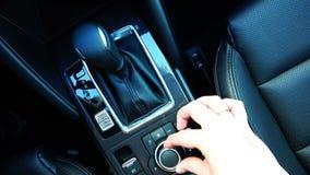 Le conducteur contrôle les arrangements du ` s de voiture près de la boîte de vitesse clips vidéos