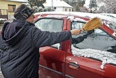 Le conducteur de femme nettoie la neige de la voiture images libres de droits