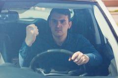 Le conducteur de jeune homme se reposant dans sa voiture derrière la roue secouant son poing menace un autre mauvais et agressif  photographie stock