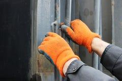 Le conducteur du camion dans les gants fonctionnants oranges, apporté le sable et les tractions l'échelle sur le corps afin d'ouv photos stock