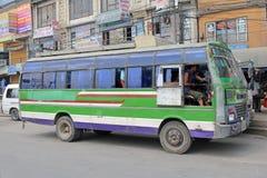 Le conducteur masculin arrête son mini autobus à l'arrêt d'autobus à Katmandou, Népal image libre de droits
