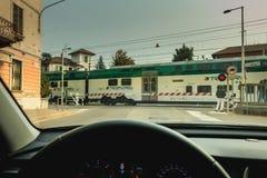 Le conducteur observe le passage d'un train derrière les portes d'un rail Image stock