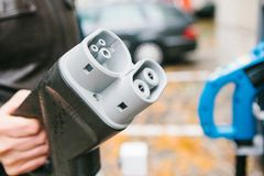 Le conducteur prend un câble pour charger le véhicule électrique Un mode de transport moderne et qui respecte l'environnement qui Images libres de droits