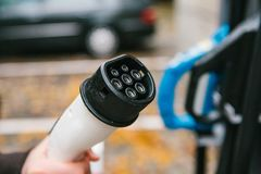 Le conducteur prend un câble pour charger le véhicule électrique Un mode de transport moderne et qui respecte l'environnement qui Photo stock